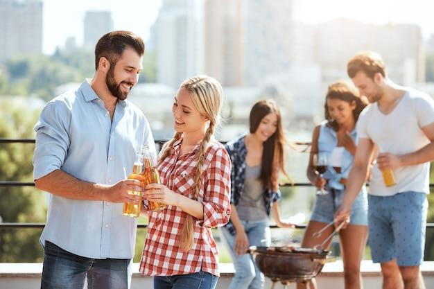 Celebrando el verano dos jóvenes amigos felices tintineando vasos con cerveza y sonriendo mientras está de pie en