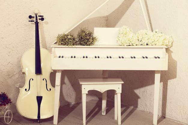 Cello blanco y piano con flores.