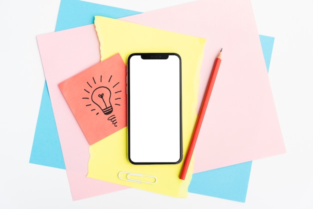 Celular de pantalla vacía y lápiz sobre papel artesanal de colores sobre fondo blanco.