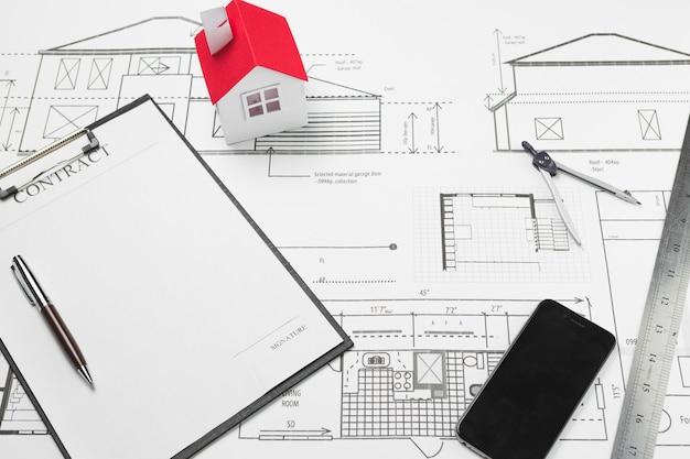 Celular y portapapeles con modelo de casa pequeña en plano