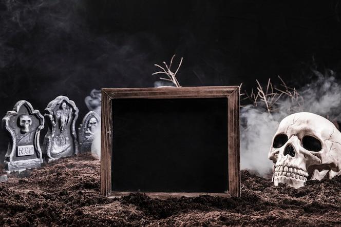 Cementerio nocturno con calavera y letrero negro