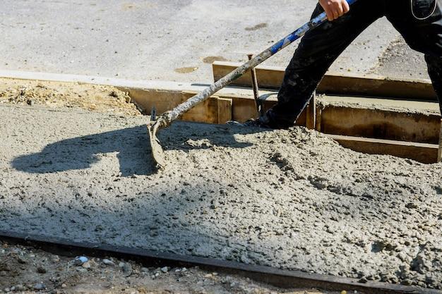 Cemento delante de la acera de un nuevo edificio en la superficie de hormigón del trabajador de la construcción en la acera nueva