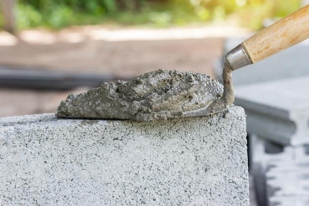 Cemento en polvo con una paleta puesta en el ladrillo para la construcción