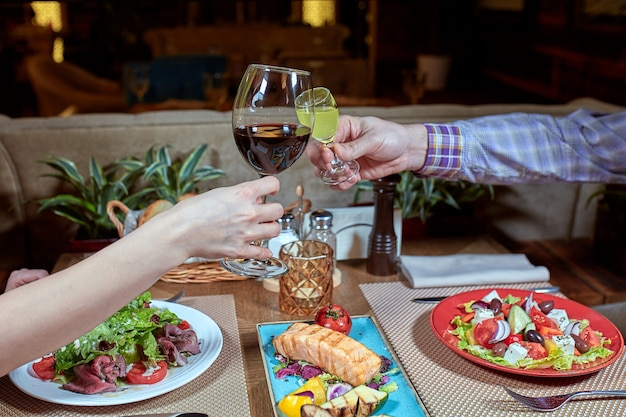 Cena con amigos de la familia servida en un restaurante. dos copas de vino blanco en manos