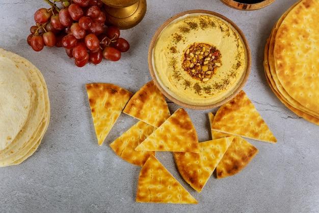 Cena árabe con pan de pita, hummus y uvas.