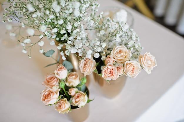 Cena de boda en el restaurante, mesas decoradas con jarrones de rosas.
