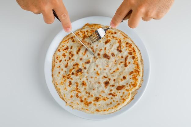 Cena comida concepto endecha plana. hombre cortando yufka turco.