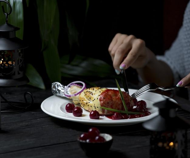 Cena, cordero de ternera en salsa de tomate con cubiertos