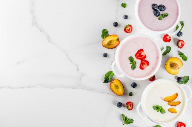 Cena de dieta saludable de verano, comida vegana, postre, varias sopas cremosas dulces de frutas y bayas