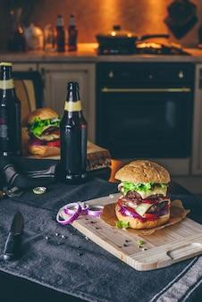 Cena con dos hamburguesas con queso y un par de botellas de cerveza en la mesa de la cocina.
