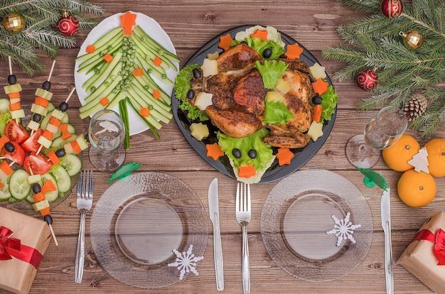 Cena festiva de navidad y año nuevo: pollo frito, árbol comestible y canapés de verduras.
