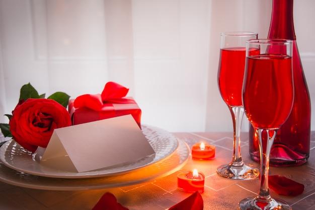 Cena festiva o romántica con rosa roja y champán.