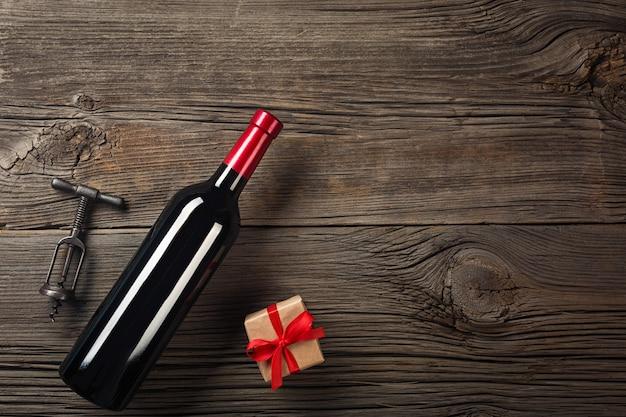 Cena festiva con vino tinto y regalo en madera rústica en vista plana