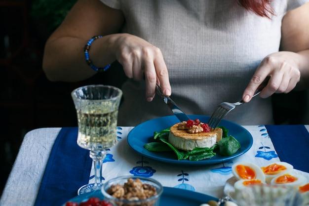 Una cena gourmet: camembert a la parrilla, una copa de vino y varios aperitivos.