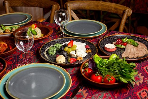 Una cena con guarnición y platos de ensalada.