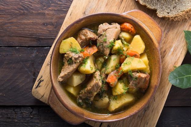 Cena irlandesa carne de res guisada con papas, zanahorias y pan de soda en mesa de madera, vista superior, espacio de copia. comida casera de invierno reconfortante - cocinada lentamente