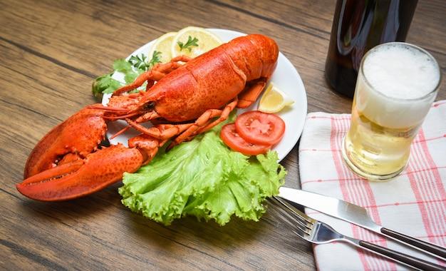 Cena de langosta de mariscos cocida al vapor en un plato de mariscos con ensalada de limón, lechuga, vegetales y tomate / cerveza en la mesa
