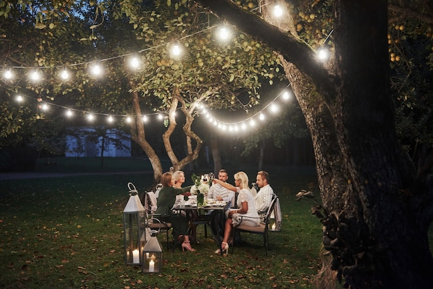 Cena de lujo hora de la tarde los amigos cenan en el hermoso lugar al aire libre.