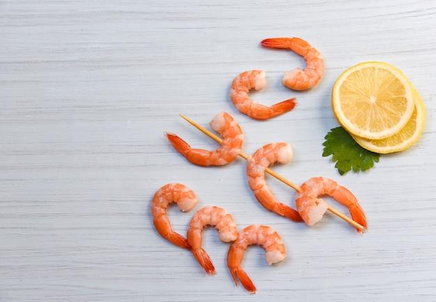 Cena de mariscos con camarones, gambas, océano, cocinado con perejil, limón y brochetas, camarones decorados sobre fondo de madera blanco