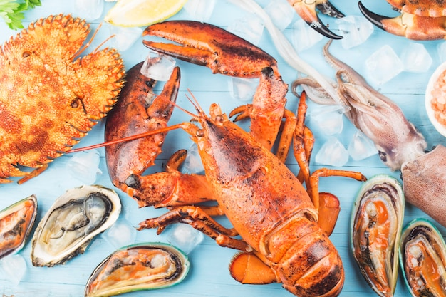 Cena de mariscos, cena de mariscos con langosta fresca, cangrejo, mejillones y ostras como fondo