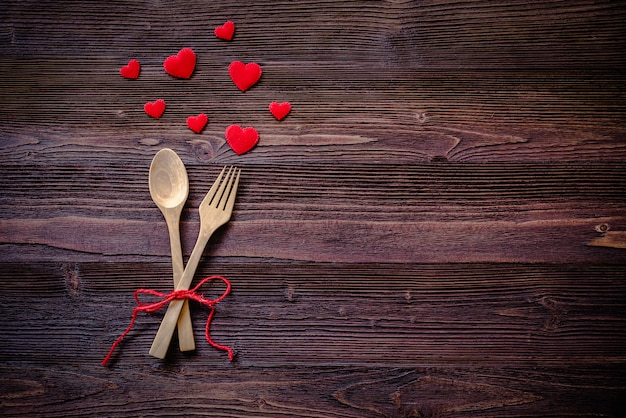 Cena con mesa en estilo rústico de madera con cubiertos, corazón rojo. día de san valentín.