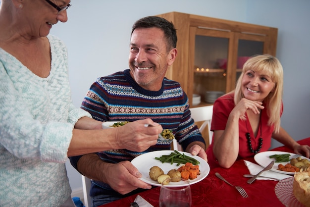Cena de navidad servida por la mujer mayor de la familia.
