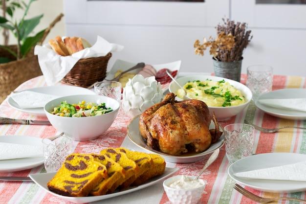 Cena navideña casera con pollo al horno, puré de papas, ensalada, bocadillos y postres.
