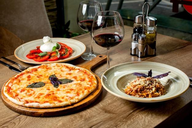 Cena con pizza margherita, ensalada, pasta y vino.