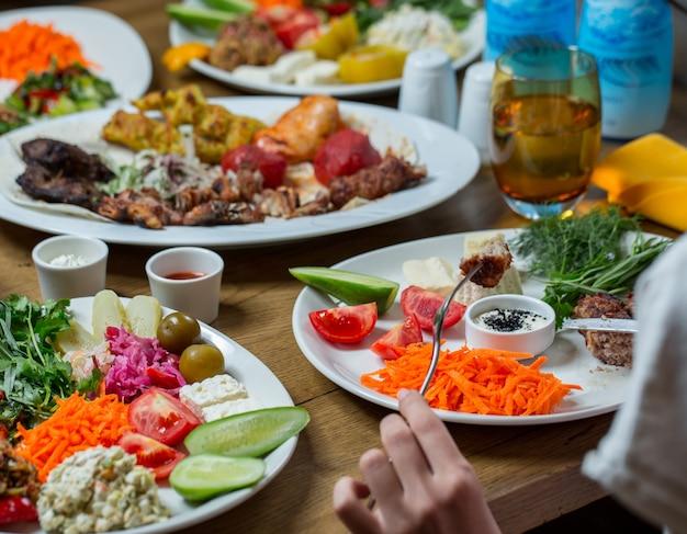 Cena en platos blancos que contienen carne y verduras, bocadillos.