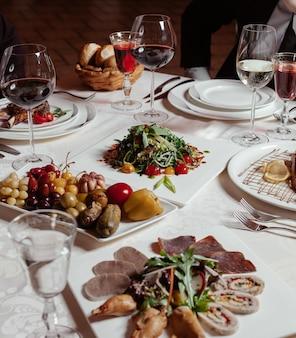 Cena preparada con vino tinto, plato de pepinillos, plato de carne, ensalada fresca