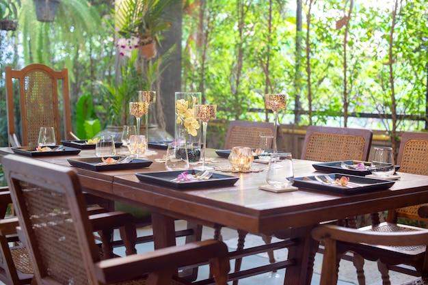 Cena puesta en la mesa de madera con larga copa de vino.