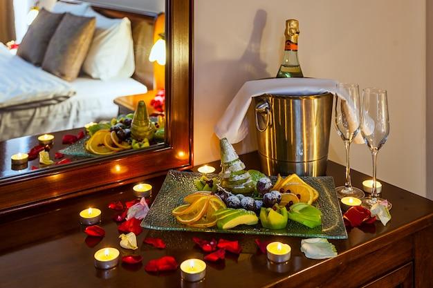 Cena romántica para los amantes: una mesa con un plato de frutas, copas de champán, champán con hielo en un cubo de metal y velas, en la pared una cama decorada con pétalos de rosa