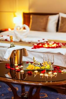 Cena romántica para enamorados una mesa con un plato de frutas, copas de champagne, champagne con hielo en un cubo de metal y velas