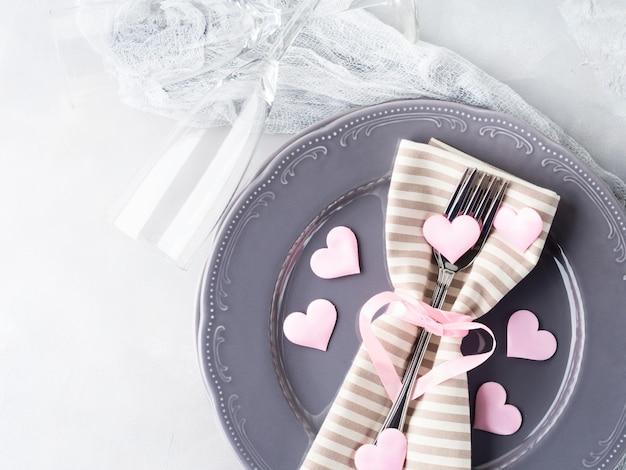 Cena romántica fecha placas corazones copas de champán en gris