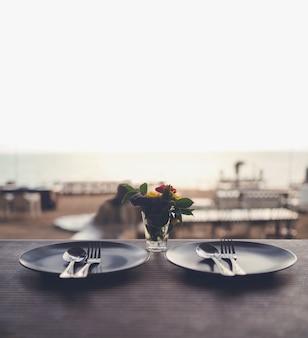 Cena romántica con hermosa vista a la playa, plato, cucharas y tenedores sobre la mesa