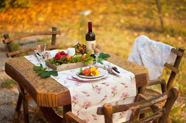 Cena romántica en el jardín de otoño, mesa para una cena agradable. vino, fruta, granada y flores. picnic al aire libre.