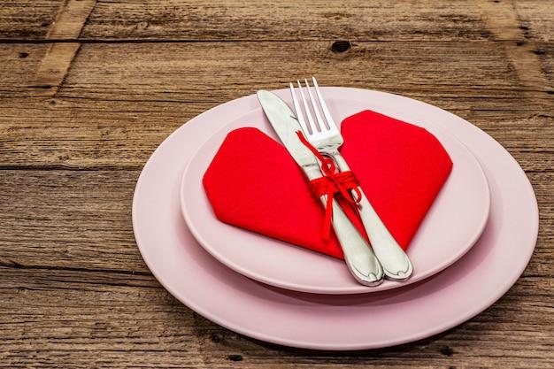 Cena romántica con platos y servilletas en forma de corazón