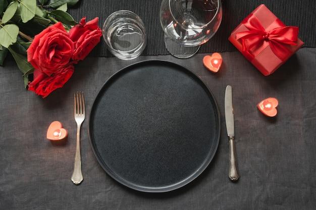 Cena de san valentín o cumpleaños. el ajuste de la tabla de la elegancia con rojo se levantó en mantel de lino negro.