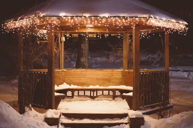 Cenador de madera con nieve en el techo en invierno