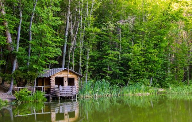 Cenador de madera en la orilla de un lago de bosque de montaña en el camino para montar ai-petri, crimea.