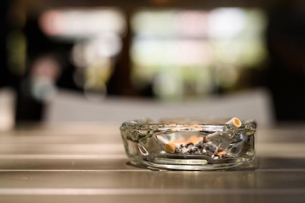 Cenicero con cigarrillos en la mesa de madera en restaurante.