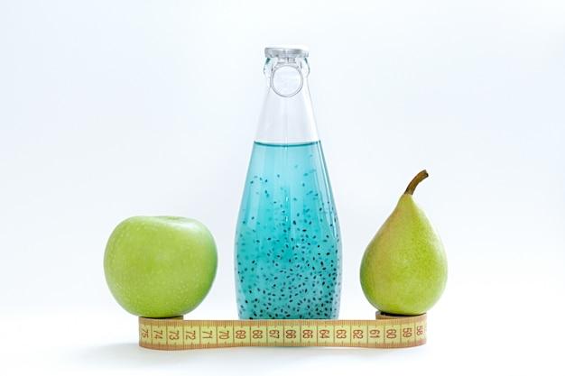 Un centímetro, una manzana, una pera y botellas de vidrio con semilla de albahaca azul sobre un fondo blanco
