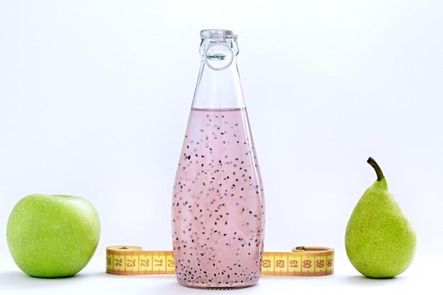 Un centímetro, una manzana, una pera y botellas de vidrio con semilla de albahaca rosa sobre un fondo blanco