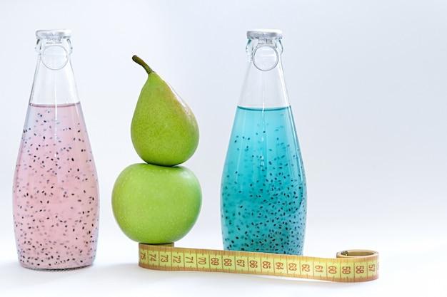 Un centímetro, una manzana, una pera y botellas de vidrio con semillas de albahaca rosa y azul sobre un fondo blanco