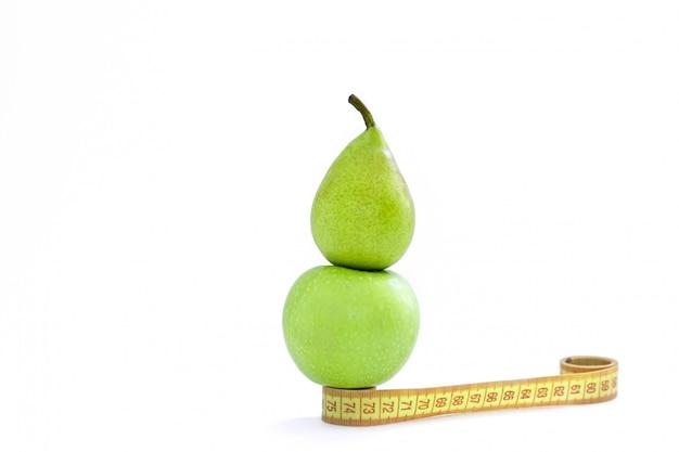 Un centímetro, una manzana y una pera verde sobre un fondo blanco