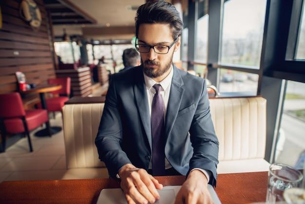 Centrado joven empresario sentado en una cafetería y trabajando en un ordenador portátil.