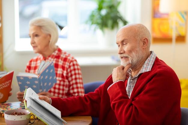 Centrado en la lectura. hombre senior pensativo tocando su barbilla mientras lee un libro interesante