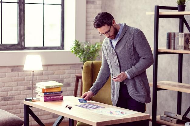 Centrado en el trabajo. buen hombre serio de pie en la mesa mientras se concentra en su trabajo