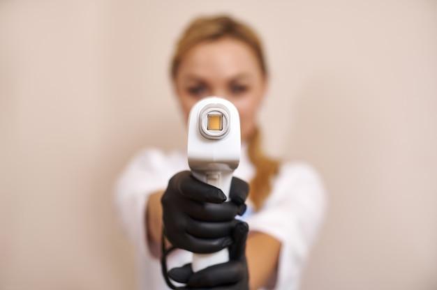 Centrarse en el aparato láser en manos de esteticista