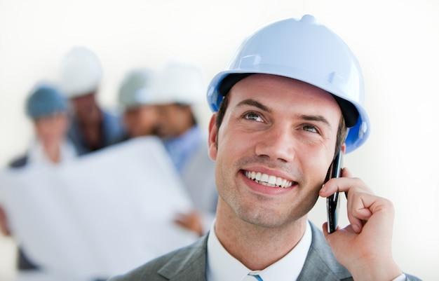 Centrarse en un arquitecto masculino con un casco en el teléfono